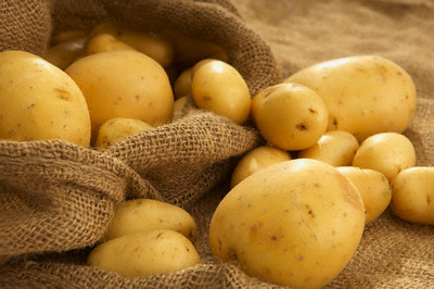 Potatoes in sack --- Image by © Peter Frank/Corbis